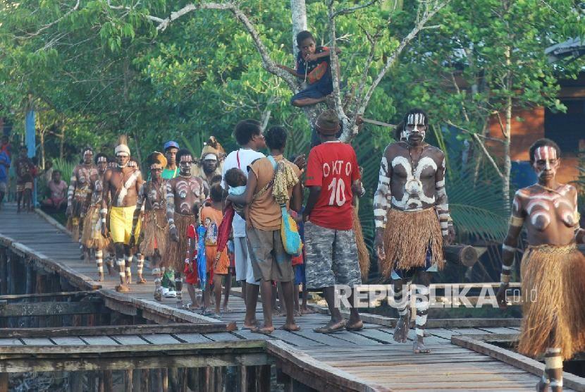 sejumlah warga suku asmat berjalan disebuah perempatan jalan yang terbuat dari papan di kabupaten asmat propinsi